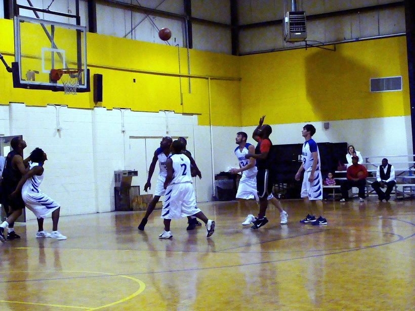 Player Shoots a Basketball and Additional Players Prepare to Rebound the Basketball